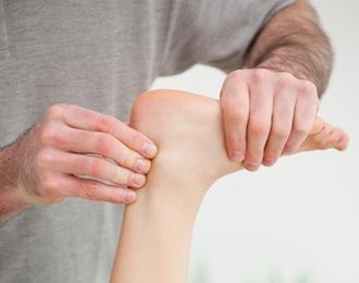 mani che toccano tendine d'Achille