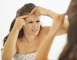 donna che si schiaccia brufolo allo specchio