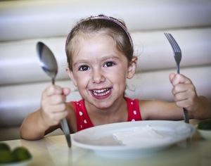 bambina con piatto e posate