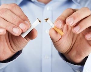 mani di uomo che spezzano sigaretta