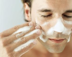 uomo che si lava viso con sapone