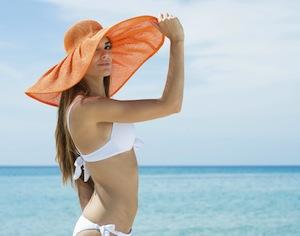 donna su spiaggia con grande cappello