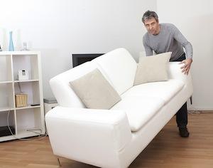 uomo che solleva divano