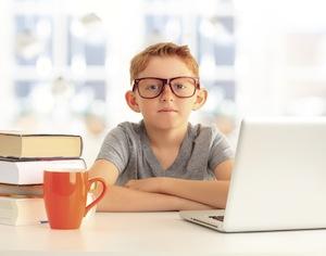 bambino con occhiali tra libri e computer